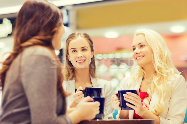 Stock photo: smiling young women with cups in mall or cafe