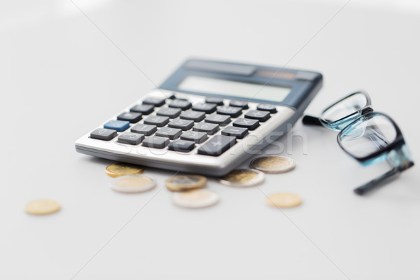 calculator, eyeglasses and coins on office table Stock photo © dolgachov