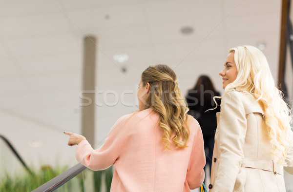 young women pointing finger on escalator in mall Stock photo © dolgachov