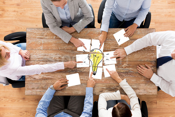close up of business team with light bulb puzzle Stock photo © dolgachov