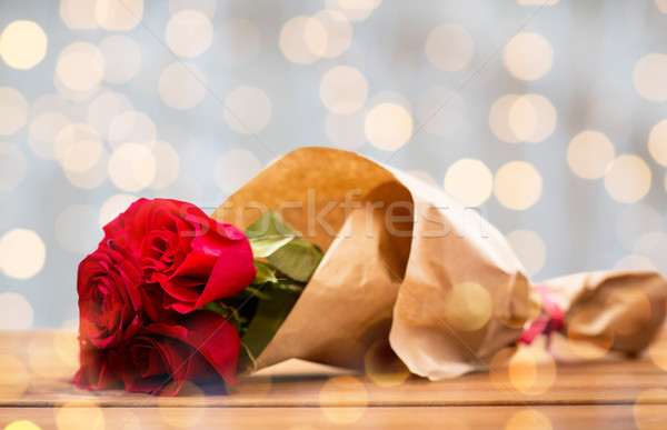 close up of red roses bunch wrapped into paper Stock photo © dolgachov