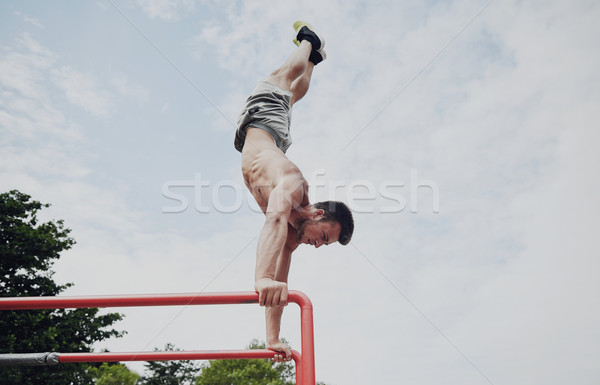 young man exercising on parallel bars outdoors Stock photo © dolgachov