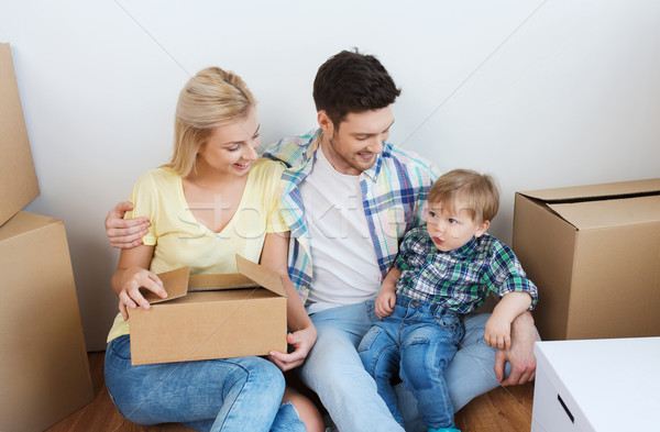 happy family with boxes moving to new home Stock photo © dolgachov