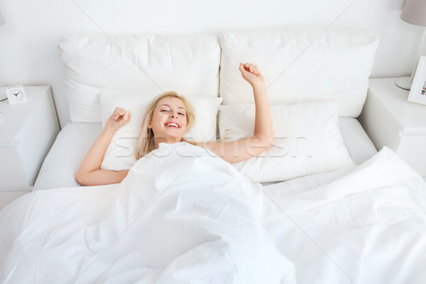 young woman stretching in bed at home bedroom Stock photo © dolgachov