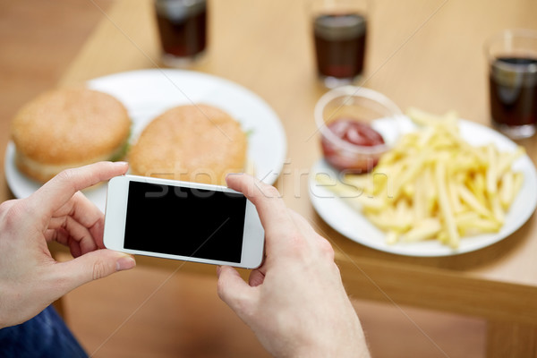 close up of man with smartphone picturing food Stock photo © dolgachov
