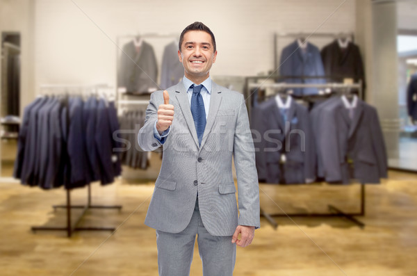happy businessman in suit over clothing store Stock photo © dolgachov