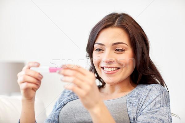 Felice donna guardando home test di gravidanza gravidanza Foto d'archivio © dolgachov