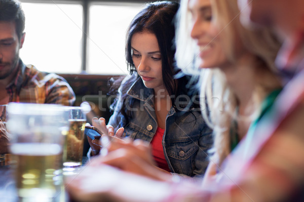 friends with smartphones drinking beer and at pub Stock photo © dolgachov