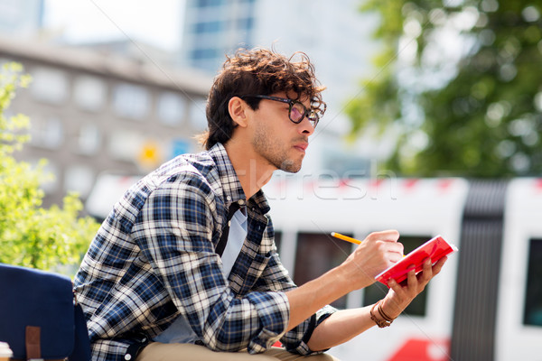 man with notebook or diary writing on city street Stock photo © dolgachov