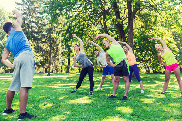 group of friends or sportsmen exercising outdoors Stock photo © dolgachov