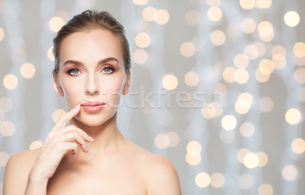 beautiful woman showing her lips over lights Stock photo © dolgachov