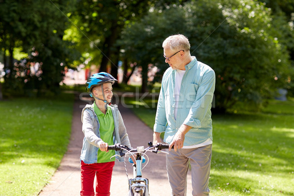 grandfather and boy with bicycle at summer park Stock photo © dolgachov