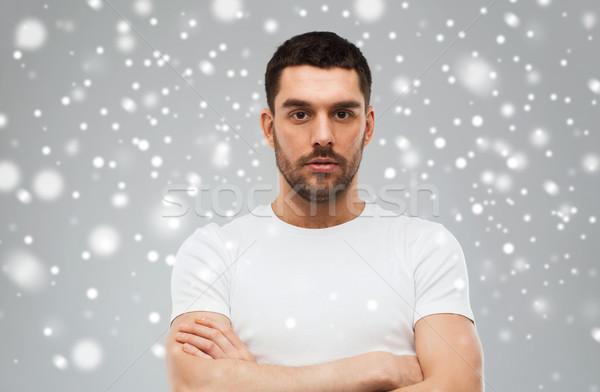 young man with crossed arms over snow background Stock photo © dolgachov