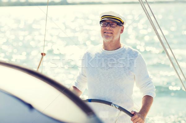 senior man at helm on boat or yacht sailing in sea Stock photo © dolgachov