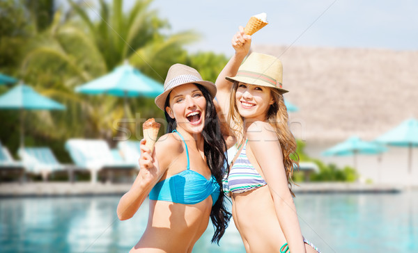 smiling women eating ice cream over swimming pool Stock photo © dolgachov