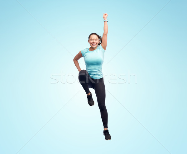 happy smiling sporty young woman jumping in air Stock photo © dolgachov