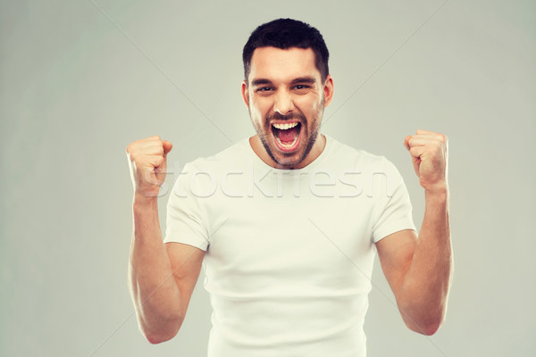 young man celebrating victory over gray Stock photo © dolgachov