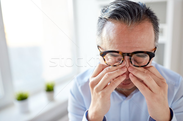 businessman in glasses rubbing eyes at office Stock photo © dolgachov