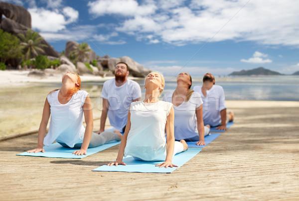Pessoas do grupo ioga praia fitness esportes Foto stock © dolgachov