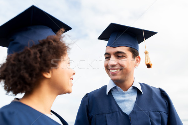 happy students or bachelors in mortarboards Stock photo © dolgachov