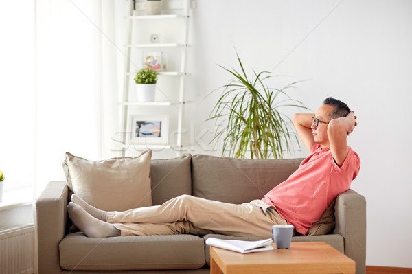 man in glasses relaxing on sofa at home Stock photo © dolgachov