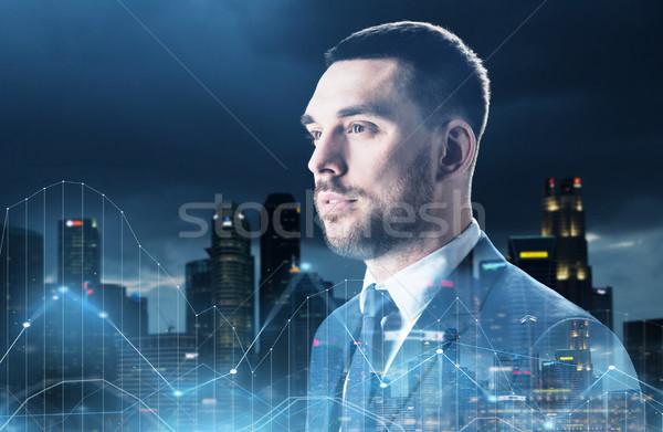 businessman over night city and diagram charts Stock photo © dolgachov