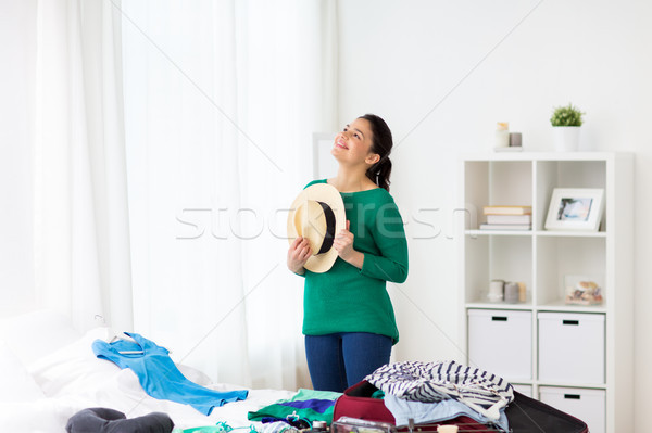 happy woman with hat packing travel bag at home Stock photo © dolgachov