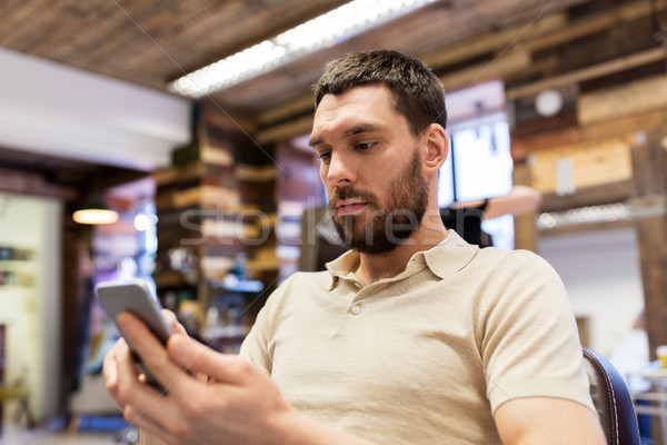 man with smartphone at barbershop or salon Stock photo © dolgachov