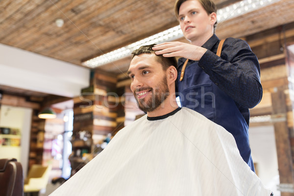man and barber styling hair at barbershop Stock photo © dolgachov