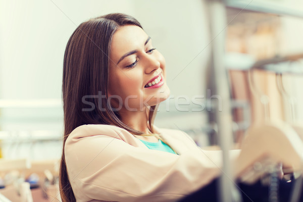 happy young woman choosing clothes in mall Stock photo © dolgachov