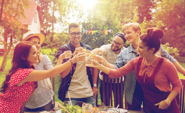happy friends having party at summer garden Stock photo © dolgachov
