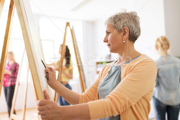 woman artist with pencil drawing at art school Stock photo © dolgachov