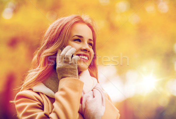 woman calling on smartphone in autumn park Stock photo © dolgachov