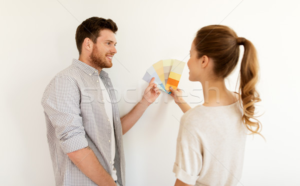 happy couple with color samples at new home Stock photo © dolgachov
