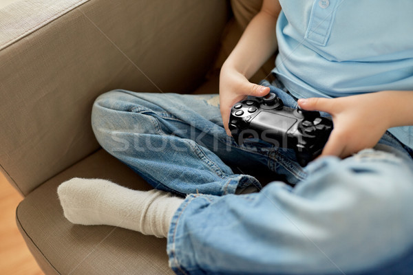 little boy with gamepad playing video game at home Stock photo © dolgachov