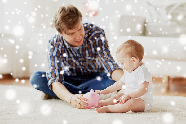 happy father with baby and piggy bank at home Stock photo © dolgachov