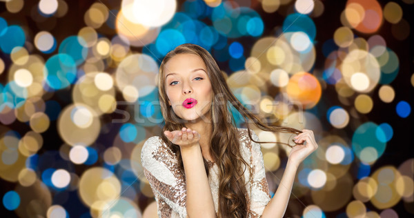 happy woman sending air kiss over party lights Stock photo © dolgachov
