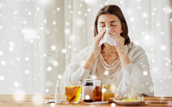 sick woman with medicine blowing nose to wipe Stock photo © dolgachov