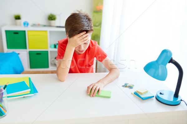 tired student boy with smartphone at home Stock photo © dolgachov