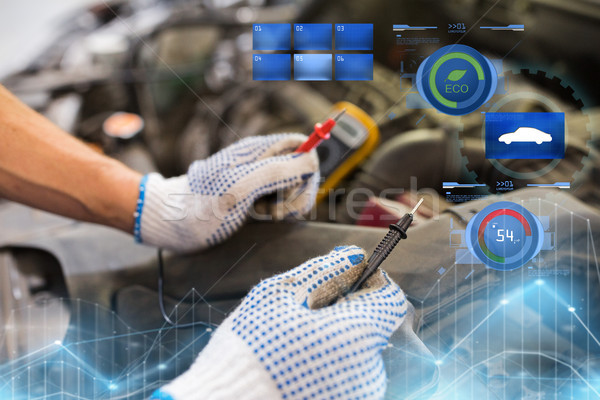 auto mechanic man with multimeter testing battery Stock photo © dolgachov