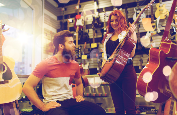 couple of musicians with guitar at music store Stock photo © dolgachov