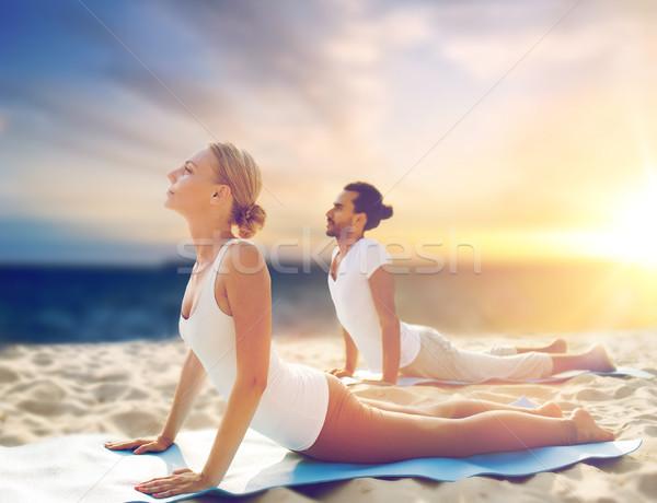 Casal ioga cobra pose praia fitness Foto stock © dolgachov