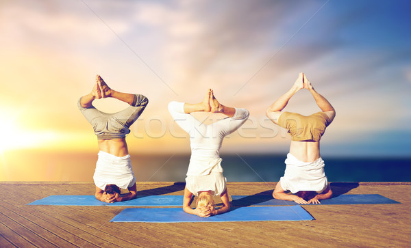 people doing yoga headstand on mat outdoors Stock photo © dolgachov