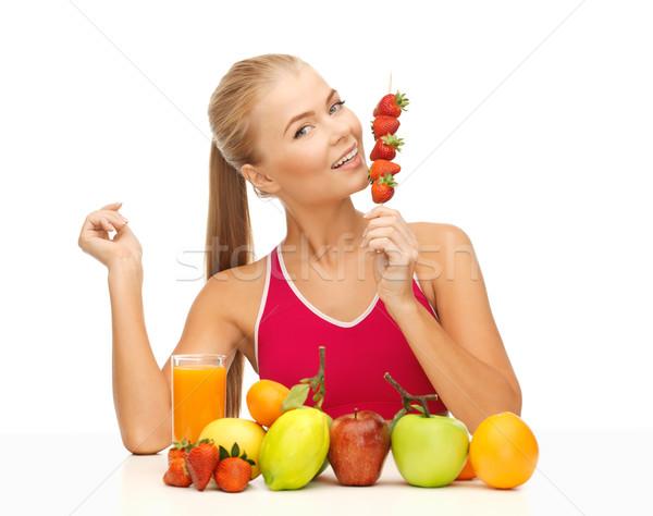 woman with organic food eating strawberry Stock photo © dolgachov