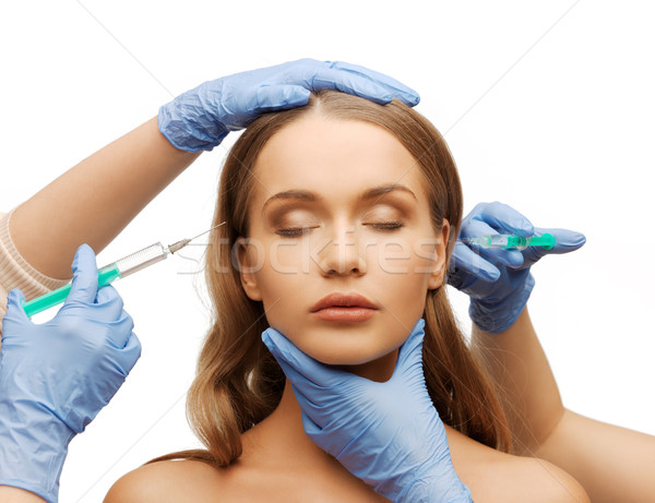 Stock photo: woman face and beautician hands with syringe