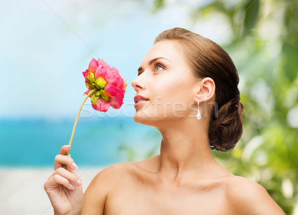 woman wearing earrings and smelling flower Stock photo © dolgachov