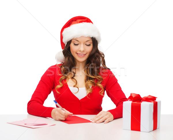 smiling woman in santa helper hat with postcard Stock photo © dolgachov