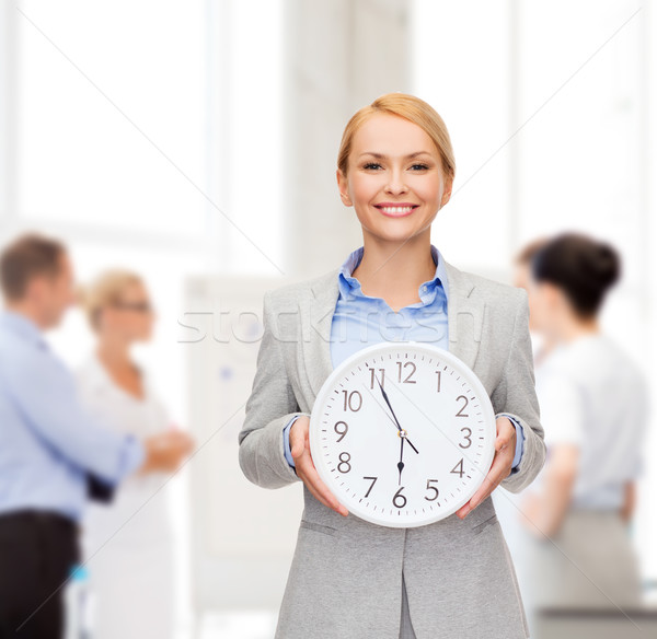 smiling businesswoman with wall clock Stock photo © dolgachov