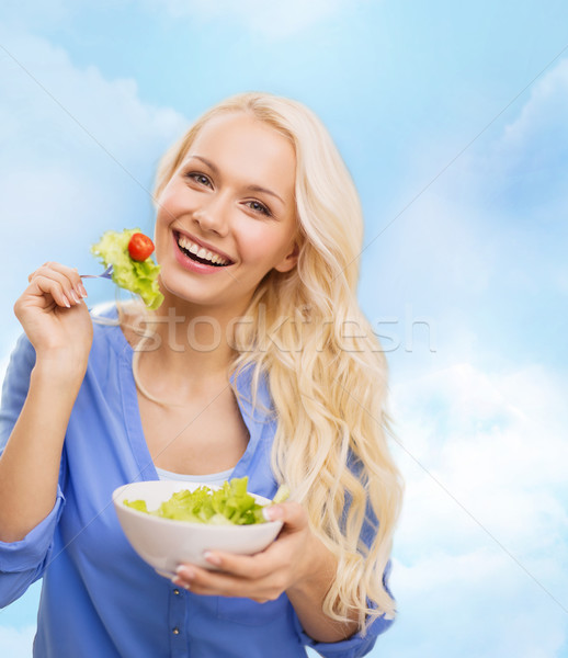 smiling young woman with green salad Stock photo © dolgachov