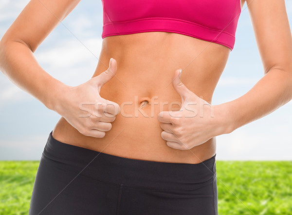 Stock photo: close up of female abs and hands showing thumbs up